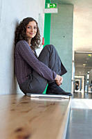 Germany, Leipzig, Young woman sitting with laptop, smiling, portrait (thumbnail)