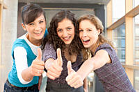Germany, Leipzig, University students showing thumbs up, smiling, portrait