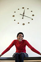 Germany, Leipzig, University student sitting against wall clock