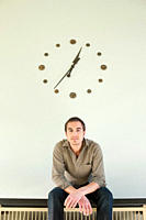 Germany, Leipzig, Mid adult man sitting against wall clock, portrait