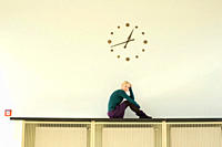 Germany, Leipzig, Young woman sitting against wall clock, portrait