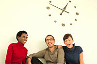 Germany, Leipzig, University students sitting against wall clock, smiling