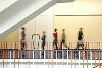 Germany, Leipzig, Group of university students walking through corridor blurred motion