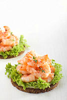 Prawns on pumpernickel with salad against white background