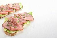 Slices of roast beef garnished with cress on rye bread.