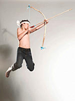 Boy 12_13 jumping with holding bow and arrow