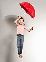 Girl 6-7 jumping with holding umbrella, smiling, portrait (thumbnail)