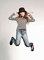 Girl 8_9 wearing hat and jumping, smiling, portrait