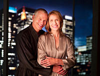 Couple in bathrobes hugging with city lights in background
