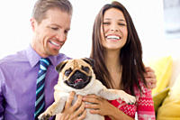 Smiling couple holding cute, small dog