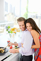 Woman hugging husband while he's cooking in kitchen