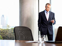 Businessman text messaging on cell phone in office