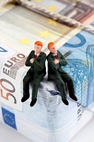Managers figurines sitting on package of euro notes
