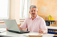 Germany, Emmering, Senior man using laptop, portrait