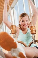 Germany, Emmering, Girl 12-13 hanging from flying rings, smiling, portrait (thumbnail)