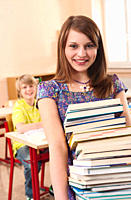 Germany, Emmering, Girl 12_13 holding stack of books with boy smiling, portrait
