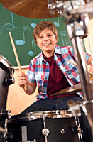 Germany, Emmering, Teenage boy 14_15 playing drumset, portrait, smiling
