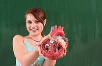 Germany, Emmering, Girl 12_13 holding heart model, smiling, portrait