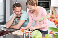 Germany, Couple preparing salad in kitchen, smiling