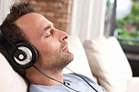 Germany, Man sitting on couch and listening music