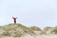 Germany, St Peter_Ording, North sea, Man standing on sand dunes with arms stretched