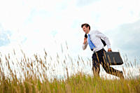 Businessman with briefcase running through long grass