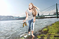 Germany, Cologne, Woman with case of beer at rhein river