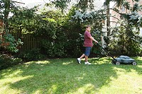 Boy mowing grass with lawnmower