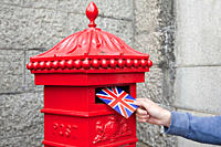 Person putting postcard in post box, London