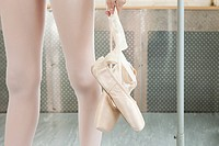 Close up on ballerina holding ballet shoes