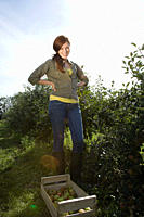 Young woman standing in apple orchard