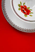 Coffee cup and saucer with floral design on red background