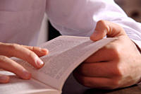 Young man reading a book, close up of hands holding the pages