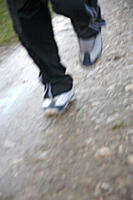 Young man jogging on a rainy day, legs close up
