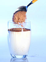 Pouring cocoa into glass of milk, close_up