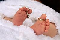 A newborn baby´s feet, with the parents´ wedding rings on his toes
