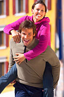 Italy, Trentino, Mature man carrying piggy back of young woman