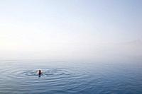 Man swimming in Cleetwood Cove  Morning mist obscures the rim and horizon line - Crater Lake National Park Oregon
