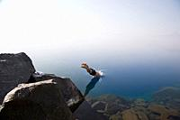 Man diving from the rocks at Cleetwood Cove  Series two of three  Morning mist obscures the rim and horizon line - Crater Lake National Park Oregon - ...