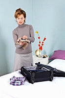 A woman packing a suitcase