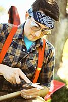 A man wearing suspenders, flannel, and a bandana sharpens a maul