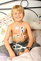 Stock photo of an 11 year old boy wearing a Holter heart monitor