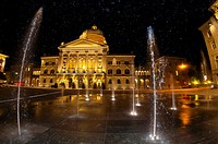 Water fountains in Bundesplatz Confederation Plaza with the Parliament Building Federal Palace of Switzerland in background at night, Bern, Canton Ber...