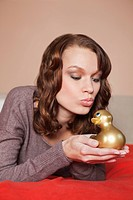 Young woman holding a rubber duck in bed