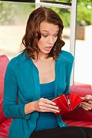 Young woman looking surprised while opening purse