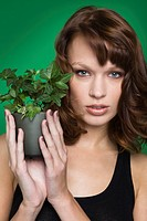 Young woman holding pot of ivy (thumbnail)