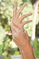 Close_up of woman's hands applying moisturizer