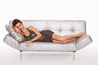 Young woman in formalwear resting on sofa