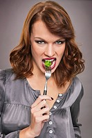 Young woman eating broccoli