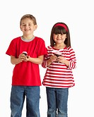 Two Children Wearing Red And Holding Cupcakes